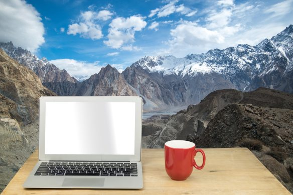 laptop and red mug on wood table with snow mountain in Pakistan